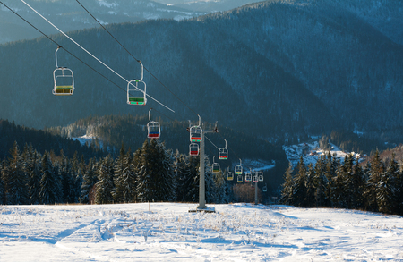 Ski lift in winter snowy mountains on the pine forest background