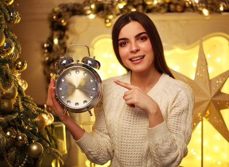 Girl with alarm clock at home in the Christmas decorations points her finger at the clock
