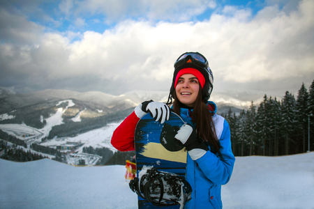 Joyful woman snowboarder in winter at ski resort on a background of mountains