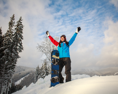 Happy girl snowboarder in the snow winter stands on top of a mountain with his arms raised to the sky