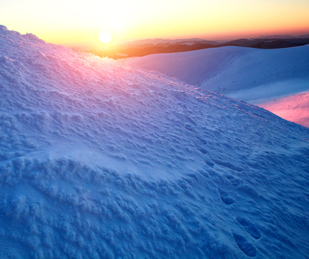 Footprints in the snow in winter mountains on background of the dawn sun leaving the horizon