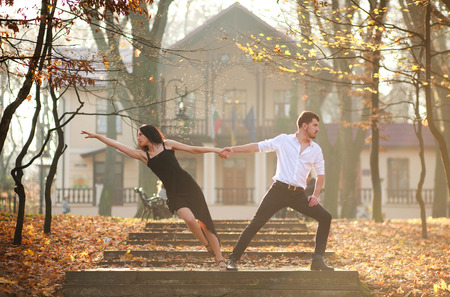 Young elegant couple man and woman passionately dancing tango in the city park at sunset