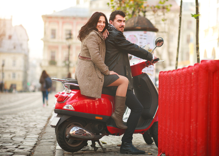 Happy young couple in love on a scooter in a tourist city