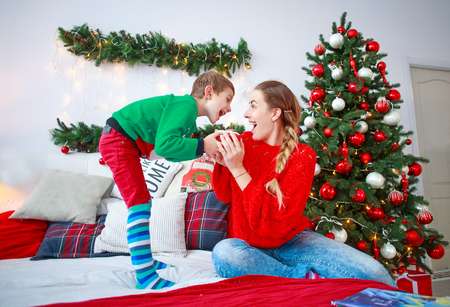Son gives a New Year's gift surprise to the happy mother at home on Christmas holiday