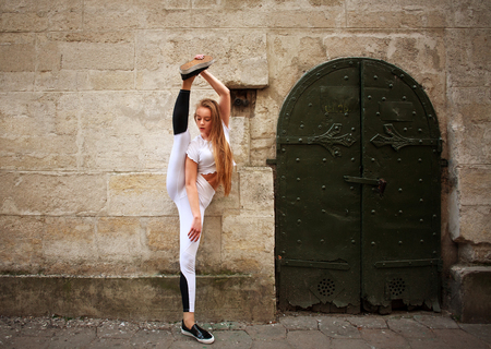 Sport athletic slim girl doing stretching exercises on the city street on background of vintage stone wall