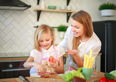 Mother with her daughter in the kitchen preparing healthy food with fresh vegetables, home parenting life style