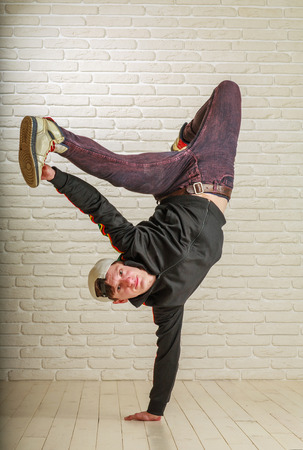 Young guy in street clothes style dancing hip-hop and breykdans in the studio on a background of a brick wall