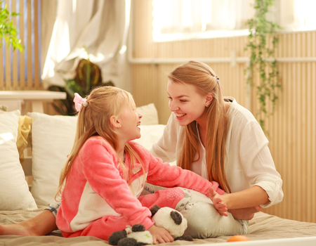 Young mother and daughter are having fun playing at home, happy family is parenthood and care