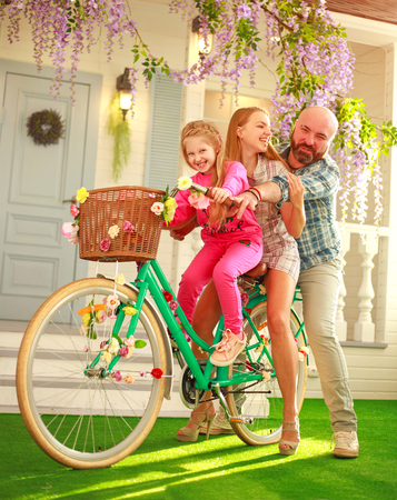 Happy parents with a child, daughter, learn to ride a bike, enjoy togetherness fun family leisure lifestyle, summer vacations at home
