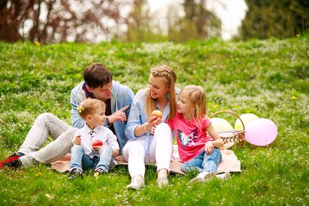 Famille heureuse sur un pique-nique dans le parc fleuri assis sur l'herbe, loisirs parentales dans la nature