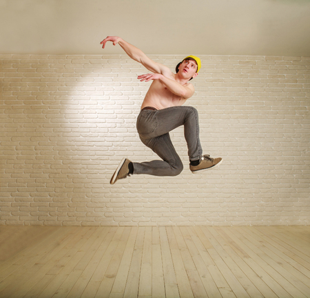 Jumping man in flight guy in hip-hop and breakdance style training workout in studio