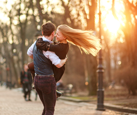 Happy young couple in love newlyweds joyfully having fun in a city park