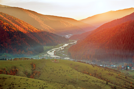 Road hiking trail in the autumn colorful mountains on background of the valley and the magnificent sunset sky