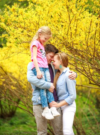 Young loving couple of parents with a child daughter in the park on the background of a yellow flowering tree