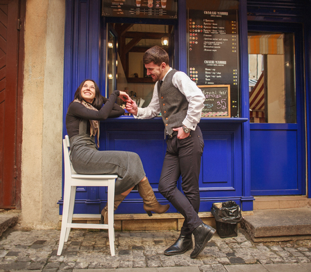 Young guy in a classic suit meets and flirting a girl near a city cafe in the old town 版權商用圖片