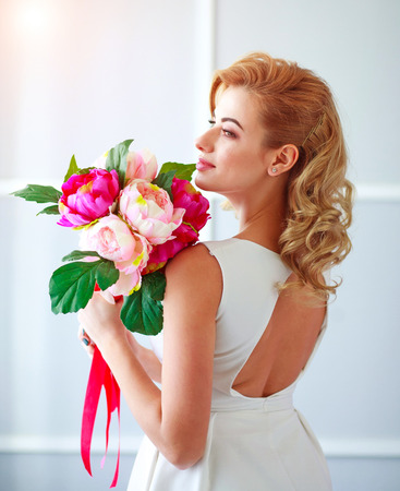 Charming happy and joyful young woman bride in a white dress with a bouquet of flowers in the studio