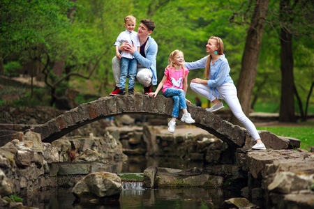 Happy young family with children in the summer green park on a stone bridge over the river on the background of the forest, parenthood vacations outdoors 版權商用圖片