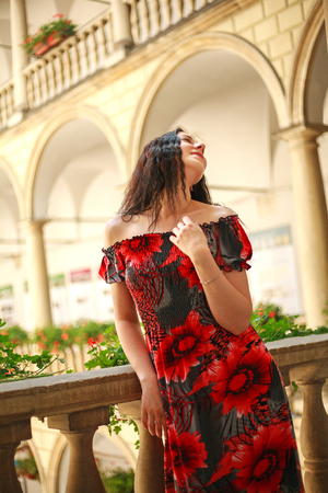 Young lady woman in a long dress in the European courtyard of the old city enjoys a sunny day 版權商用圖片