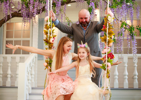 Joyful family parents with their daughter at home in a blooming garden on a swing
