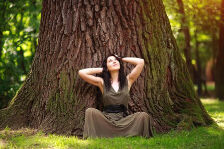 Girl in dress sits enjoying nature meditates, practices yoga in a forest park