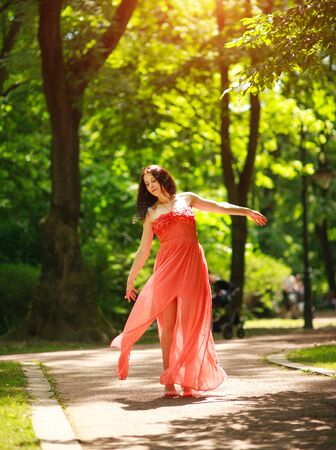 Joyful young woman in a green city park on the nature among the trees enjoys dancing, concept of freedom and carelessness
