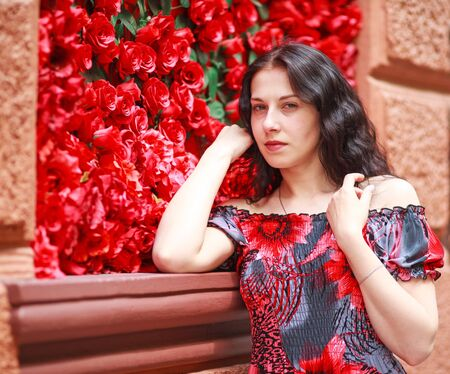 Portrait of elegant dreamy woman in a dress on a red roses background Stok Fotoğraf