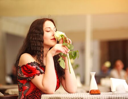 Girl in dress sitting at a table in the restaurant and enjoy the scent of roses flower awaiting a date