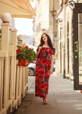 Joyful lady woman in a long beautiful dress is walking along the street of an old European city