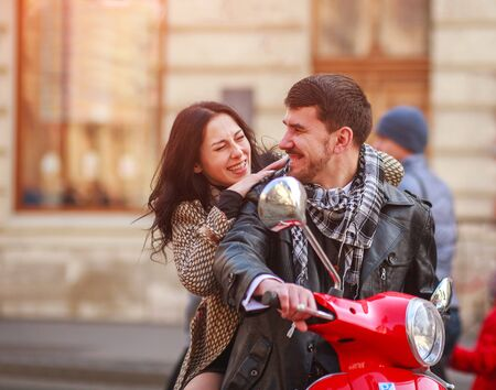 Happy young couple riding a scooter bike in the autumn city together