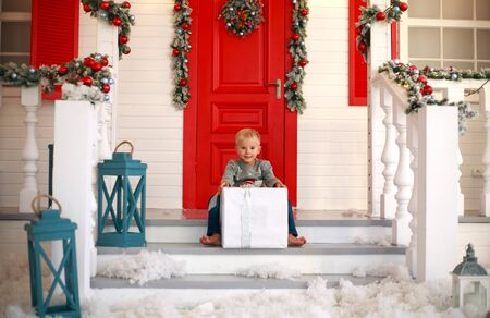 Little boy child with a gift in the yard at home in Christmas decorations