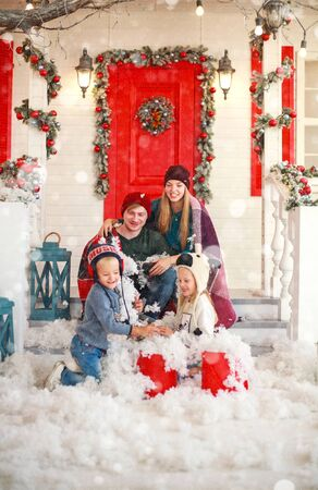 Joyful family with children playing snowballs in the courtyard of a snowy house in winter on Christmas Stockfoto