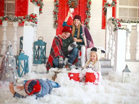 Joyful family with children playing snowballs in the courtyard of a snowy house in winter on Christmas