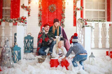 Vrolijke familie met kinderen die sneeuwballen spelen op de binnenplaats van een besneeuwd huis in de winter met Kerstmis Stockfoto