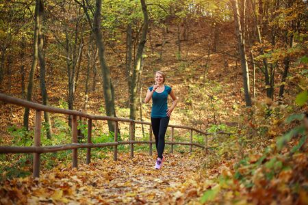 Young slender woman runs in a forest park, healthy lifestyle outdoors in nature