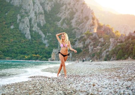 Lovely young woman on a pebble beach of the Mediterranean Sea on a background of green mountains