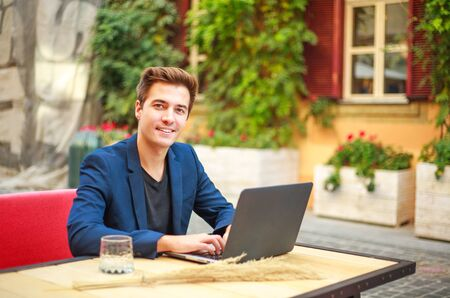 Charming young business man outdoors at a table in a summer cafe courtyard working at a laptop