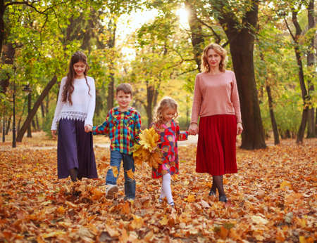 Happy family, mother with children, daughters and son are walking through the fallen leaves of the autumn city forest park
