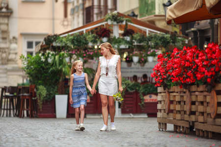 Mother and daughter walk together cheerfully in the historic square of the old tourist town