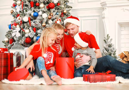 Young family at christmas, with new year gifts at home in holiday decorations