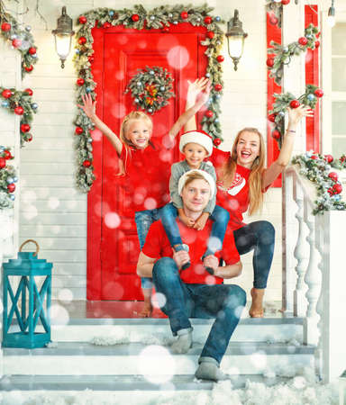 Happy family in Christmas in yard of New Year's decoration house, tradition of celebrating