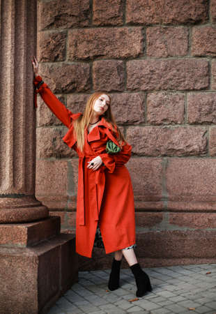Elegant woman in a terracotta coat on the street of an old European city Stockfoto