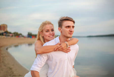 Joyful loving young newlywed couple in each other's arms on the city beach Stock fotó