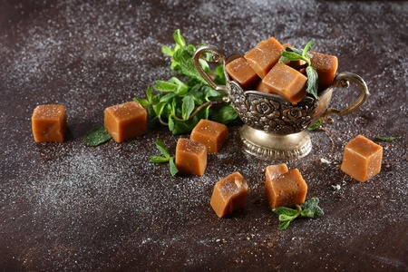 Homemade caramel in vintage bowl wiStill life cth mint. Brown background.