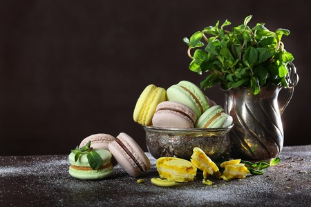 Macaroons cakes in vintage dishes on a brown background.
