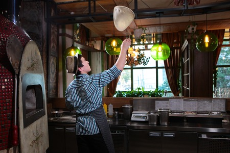 A young guy, a pizza maker throws up a pizza dough. The guy is standing with his back, his face is not visible. The interior of the restaurant or cafe.
