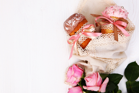 Pink porcelain cup of tea with a saucer on a white background, with pink roses and two Easter cakes. Easter holiday concept. There is free space for the inscription. Stockfoto