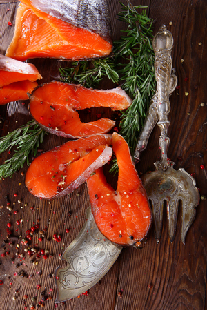 Chunks of red fish with rosemary on a wooden background with silver-plated vintage instruments. Brown background. 写真素材