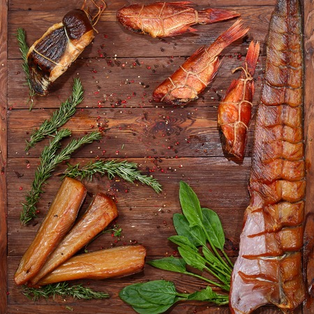 Whole smoked fish and pieces on a brown wooden background. Rosemary and spinach close up on wooden background. View from above. Stok Fotoğraf