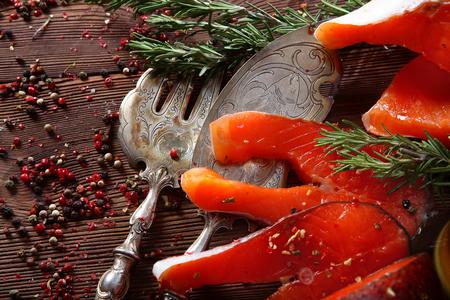Bocconcini di pesce rosso al rosmarino su fondo in legno con strumenti vintage argentati. Sfondo marrone.