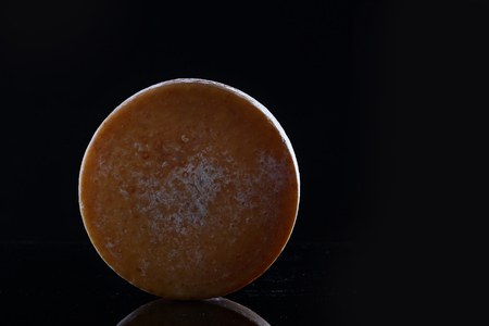 Round head of hard cheese on a black background. Copy space.Black background